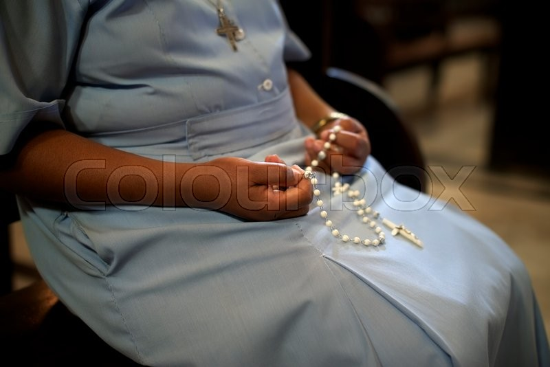 People and religion, catholic sister praying in church and holding cross in hands. With model release, stock photo