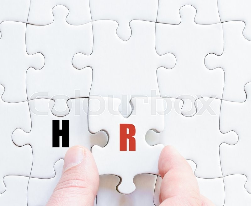 Hand of a business man completing the puzzle with the last missing piece.Concept image of Business Acronym HR as Human Resources, stock photo