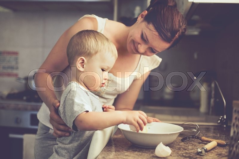 Mom with her 2 years old child cooking holiday pie in the kitchen to Mothers day, casual lifestyle photo series in real life interior, stock photo