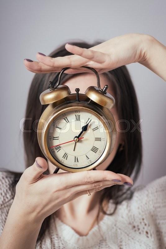 Girl holding a clock, stock photo