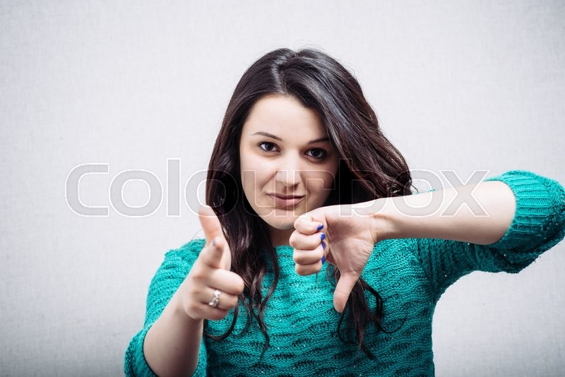 Girl shoots a finger and points down, stock photo