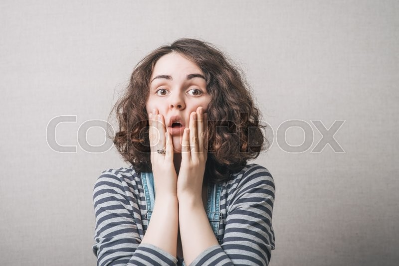 The woman thought, sad, thinking, emotions, fear. On a gray background, stock photo