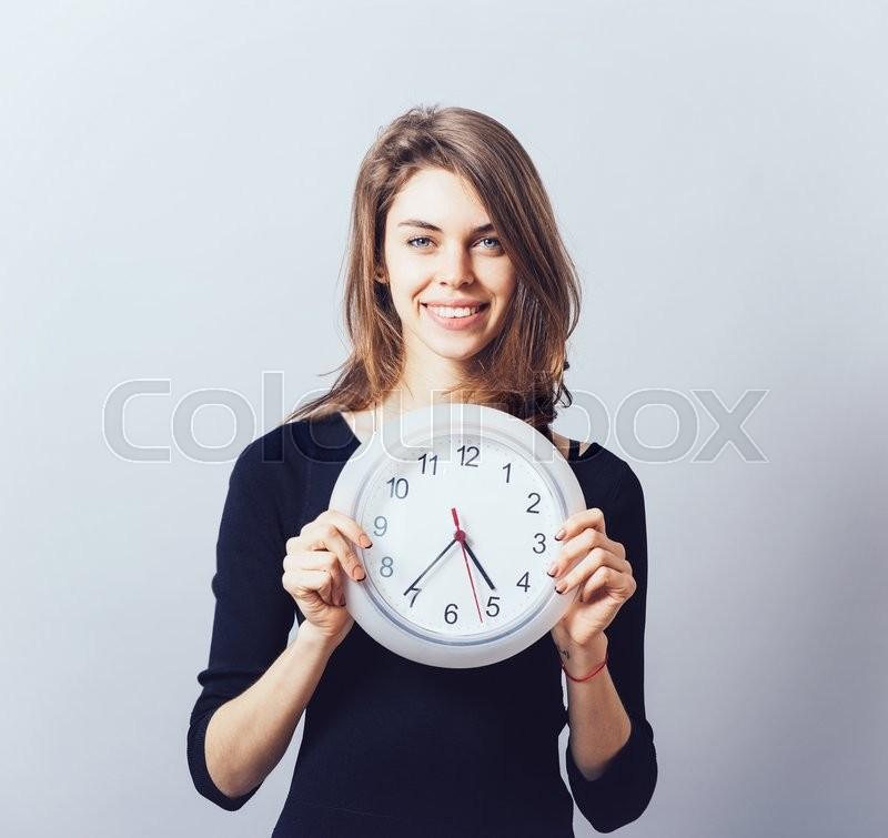 Beautiful smiling woman holding big clock, stock photo