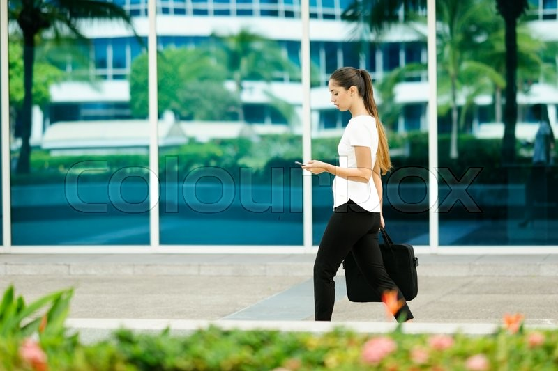 Cropped view of business woman walking in city street with laptop bag, chatting on mobile phone and going to work in the morning, stock photo