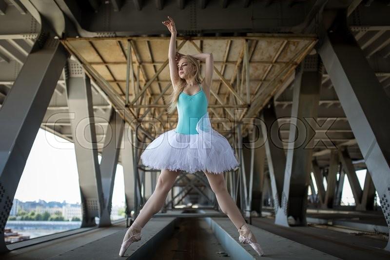 Graceful ballerina in white tutu in the industrial background of the bridge, stock photo