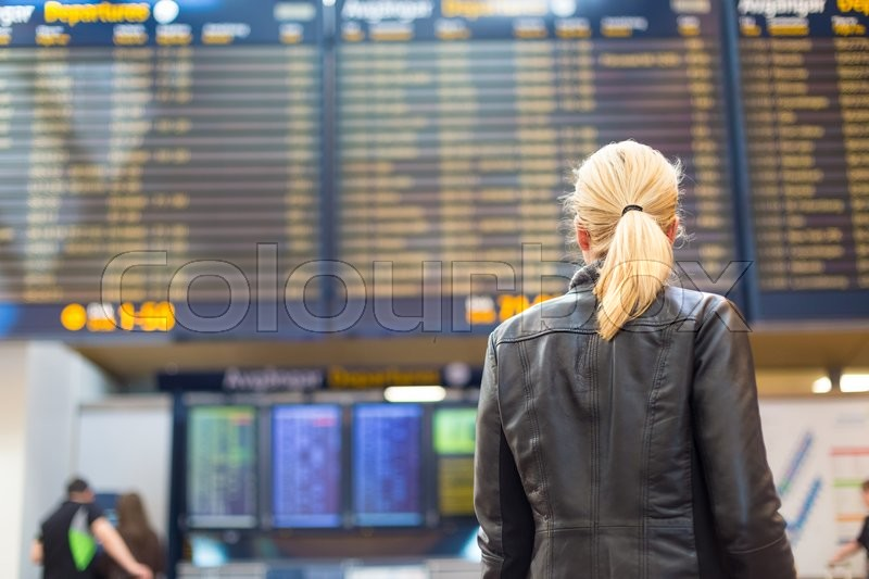 Casually dressed young stylish female traveller checking a departures board at the airport terminal hall in front of check in couters. Flight schedule display blured in the background. Focus on woman, stock photo