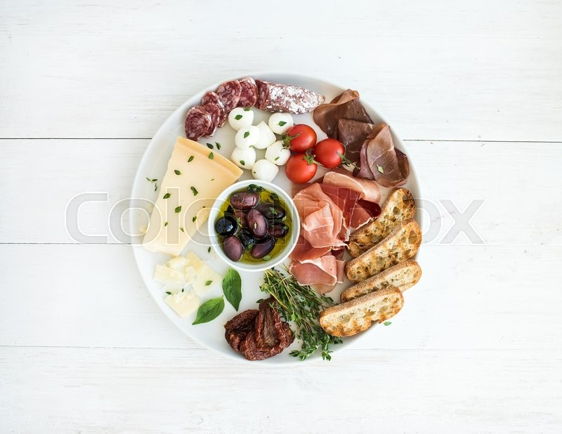 Wine appetizer set. Cherry-tomatoes, parmesan cheese, meat variety, bread slices, dried tomatoes, olives and basil on round ceramic plate over white wood backdrop, top view, stock photo