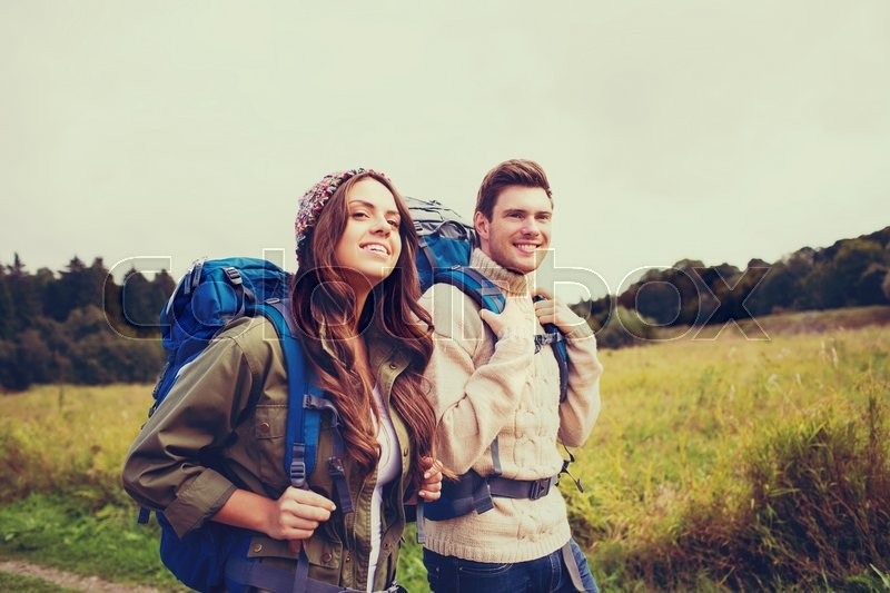 Adventure, travel, tourism, hike and people concept - smiling couple walking with backpacks outdoors, stock photo