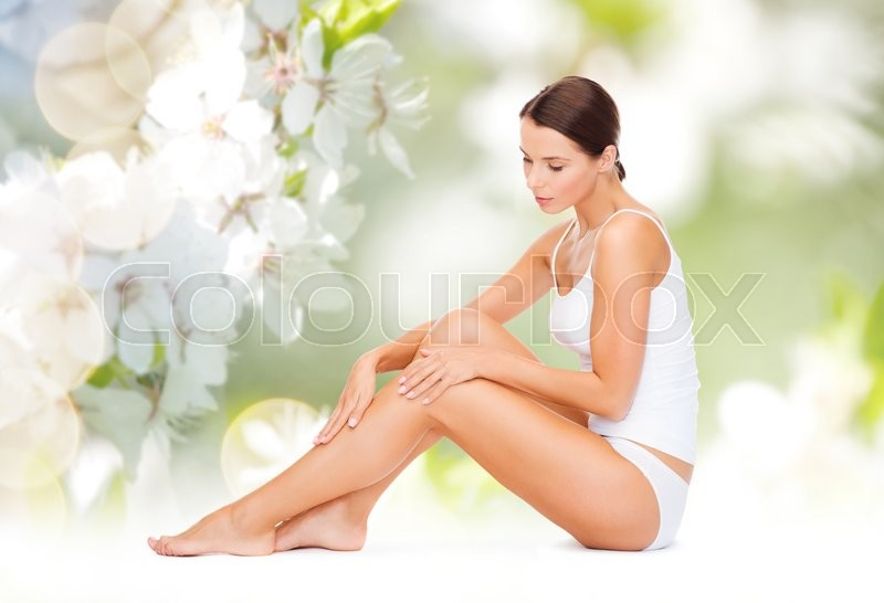 People, beauty and body care concept - beautiful woman in cotton underwear touching legs over green natural cherry blossom background, stock photo