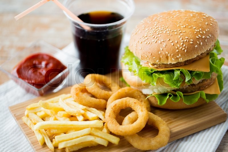 Fast food and unhealthy eating concept - close up of hamburger or cheeseburger, deep-fried squid rings, french fries, coca cola drink and ketchup on wooden table, stock photo