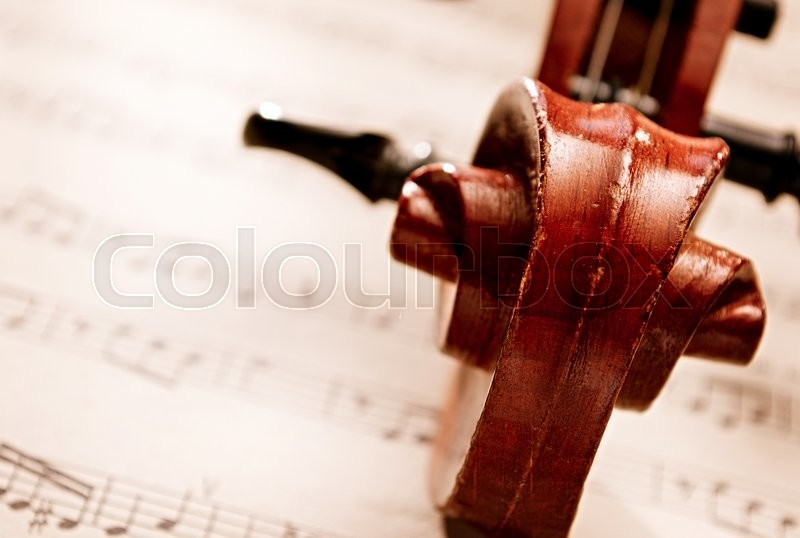 High Angle View Close Up of Carved Wooden Violin Scroll Resting on Top of Sheet Music Composition, Musical Still Life with Copy Space, stock photo