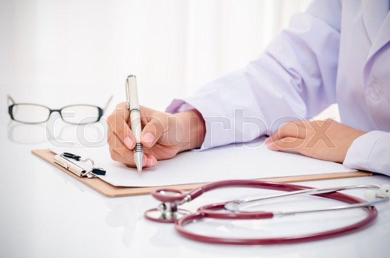 Doctor writing record on folder on desk in office, stock photo