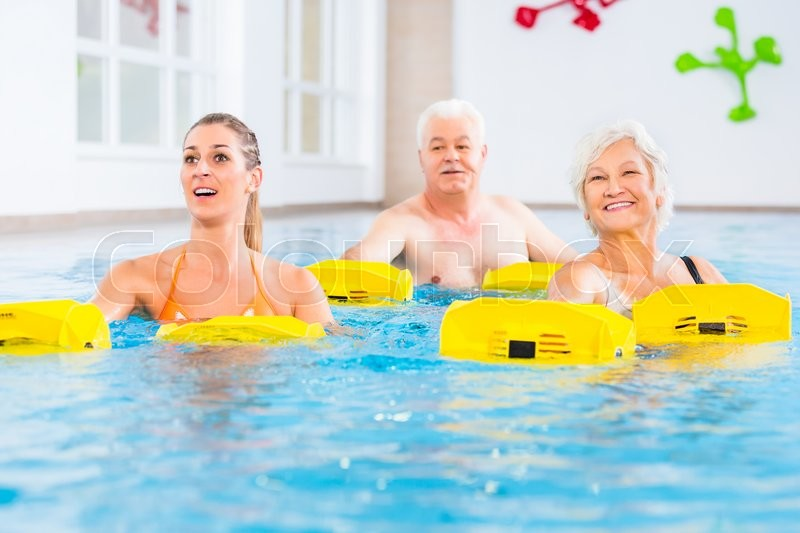 Senior and young people in water gymnastics with resistance device, stock photo