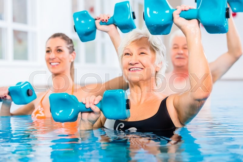 People young and senior in water gymnastics physiotherapy with dumbbells, stock photo