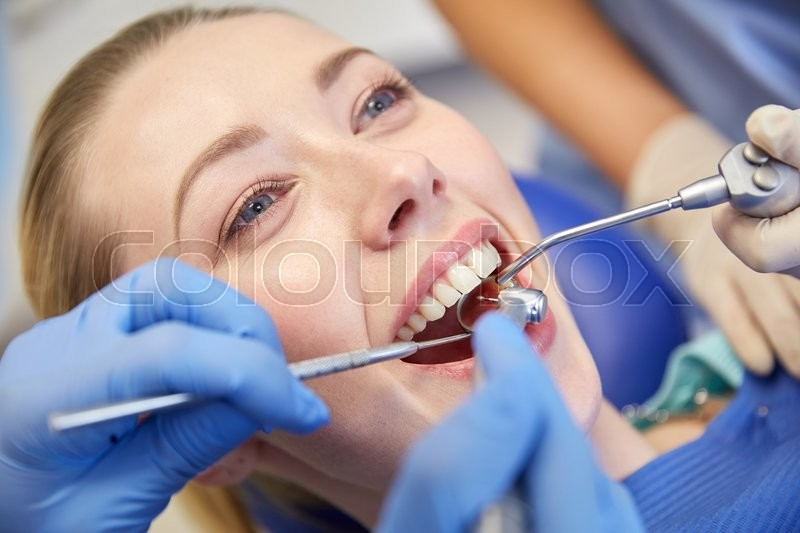 People, medicine, stomatology and health care concept - close up of dentists and assistant with mirror, drill and dental air water gun spray treating female patient teeth at dental clinic, stock photo