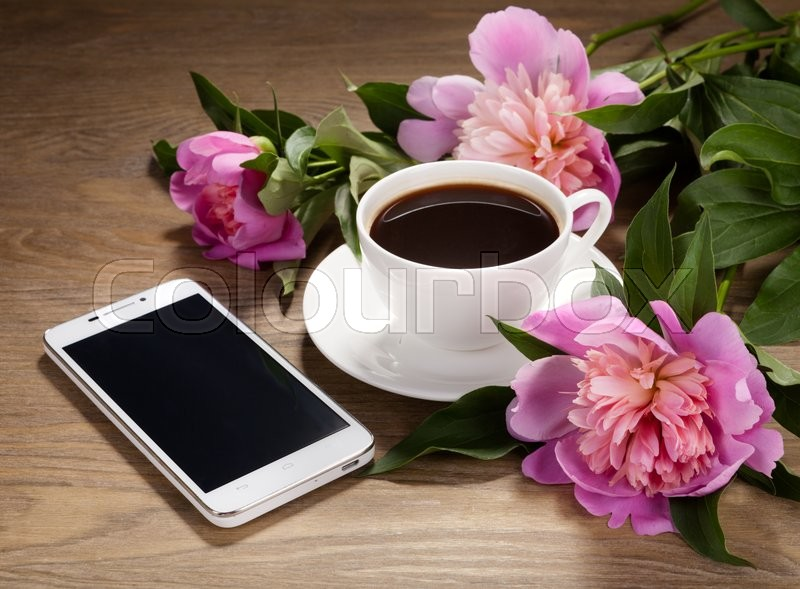 Smartphone, a cup of coffee and flowers on old table, stock photo