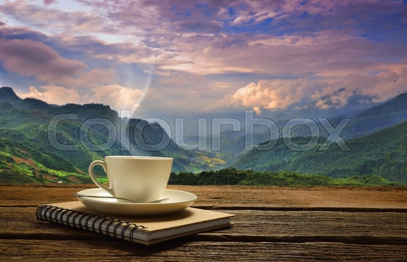 Morning cup of coffee with mountain background at sunrise, stock photo