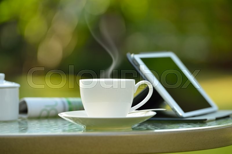 Cup of coffee with smoke and tablet computer in garden, stock photo