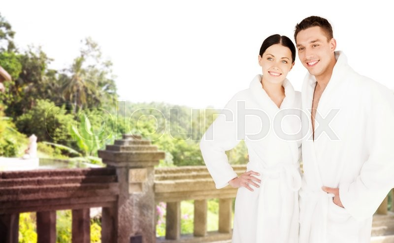 People, travel, tourism, vacation and honeymoon concept - happy couple in bathrobes over spa hotel resort background, stock photo