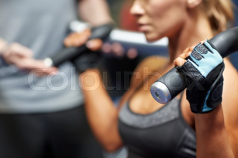 Sport, fitness, bodybuilding, teamwork and people concept - young woman and personal trainer flexing muscles on gym machine, stock photo