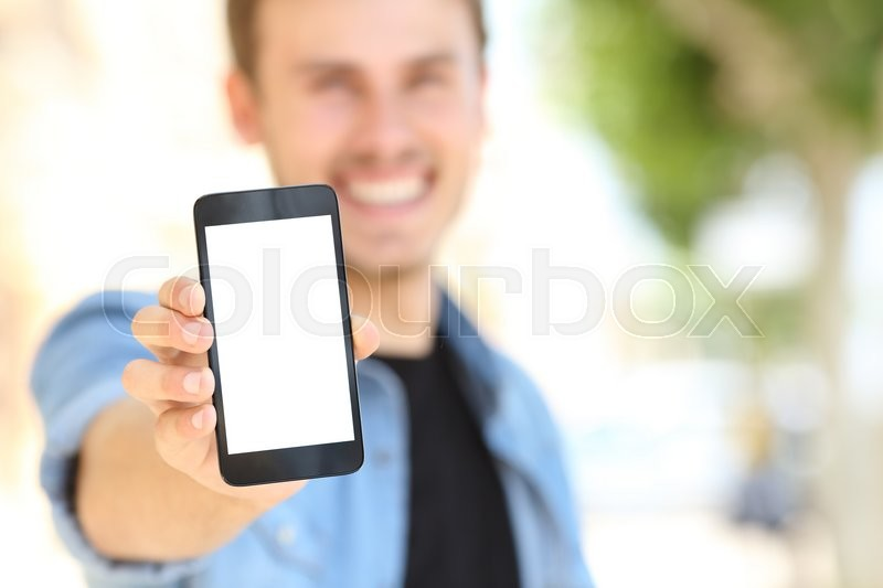Unfocused man hand showing to you a blank phone screen in the street, stock photo