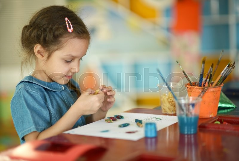 Little girl drawing with paints at home, stock photo