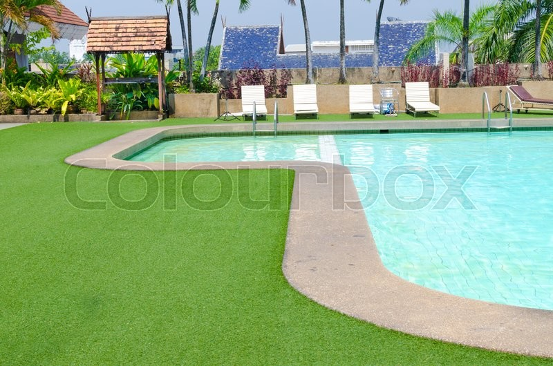 Swimming pool with green grass and palm at hotel close up , stock photo
