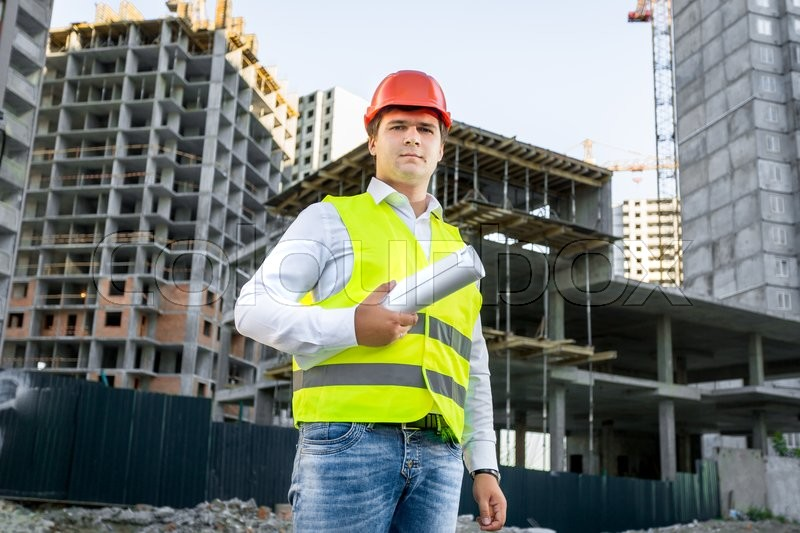 Portrait of architect in red hardhat posing on building site, stock photo