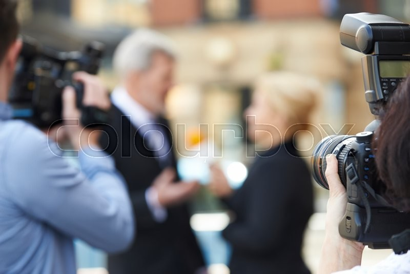 Photographer Taking Pictures Of Female Journalist Interviewing Businessman, stock photo