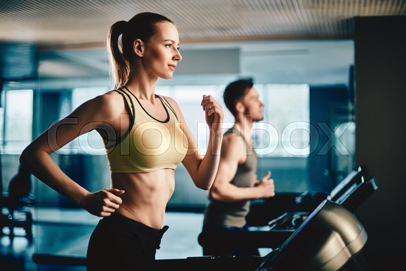 Pretty woman running on treadmill with fit young man on background, stock photo