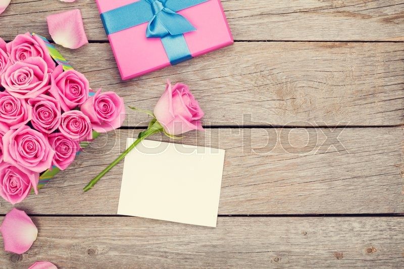 Valentines day greeting card or photo frame and gift box full of pink roses over wooden table. Top view, stock photo