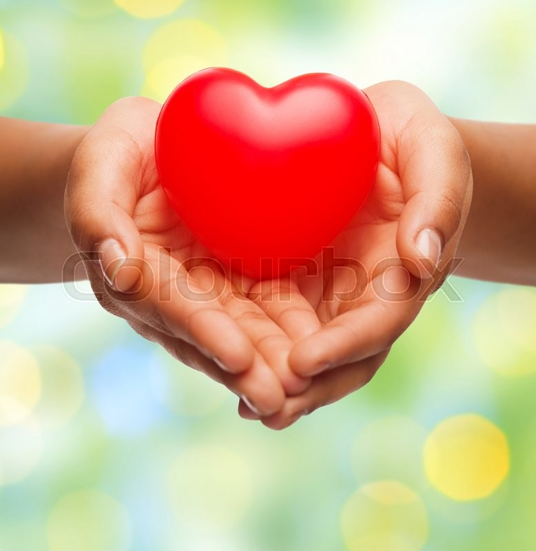 Health, medicine, love, valentines day and charity concept - close up of african american female hands holding small red heart over green lights background, stock photo