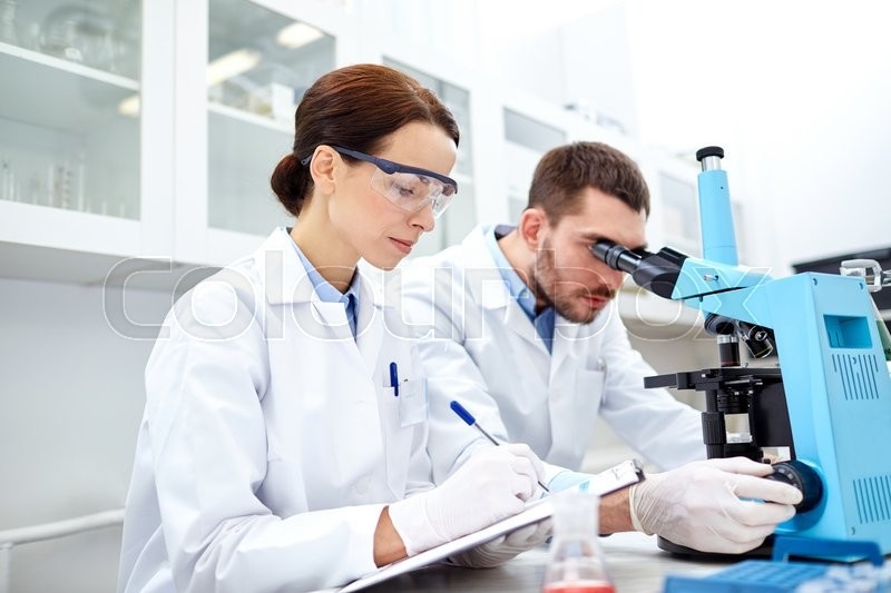 Science, chemistry, technology, biology and people concept - young scientists shaking glass with reagent and making test or research in clinical laboratory, stock photo