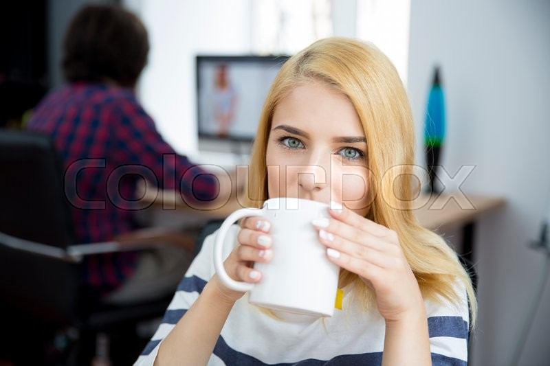 Young casual woman drinking coffee in office, stock photo