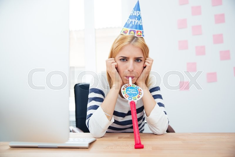 Young girl sitting at the table with party hat in office and blows whistle, stock photo