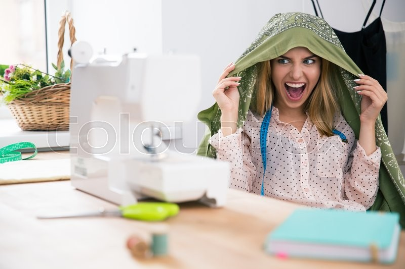 Funny female deisgner sitting at her workplace and screaming, stock photo