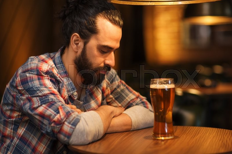 People, loneliness, alcohol and lifestyle concept - unhappy single man with beard drinking beer at bar or pub, stock photo