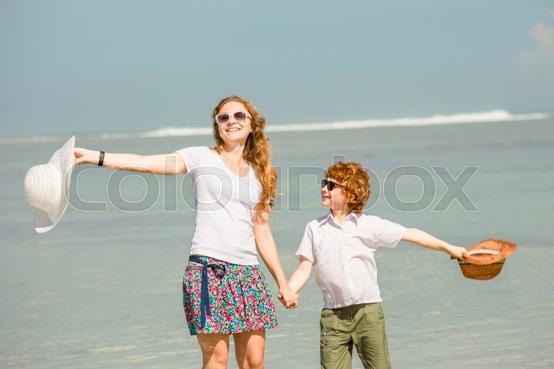 Mother and red haired son having family time on holidays walking along the beach. Travel, holiday, vacation concept , stock photo