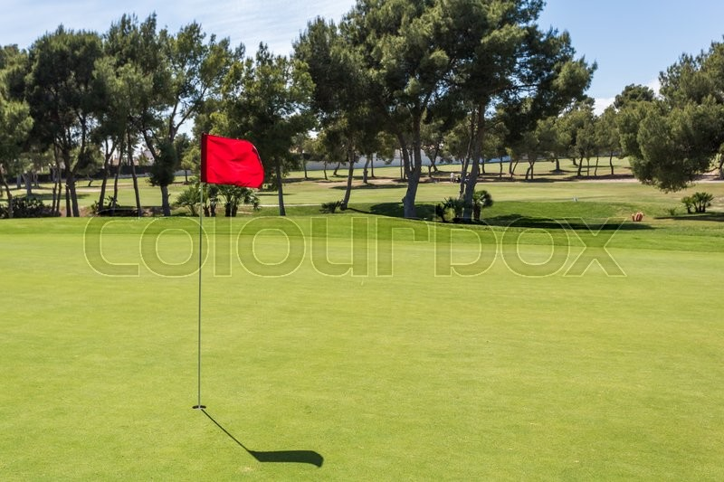 Red flag in the hole on a green golf field golf course, stock photo