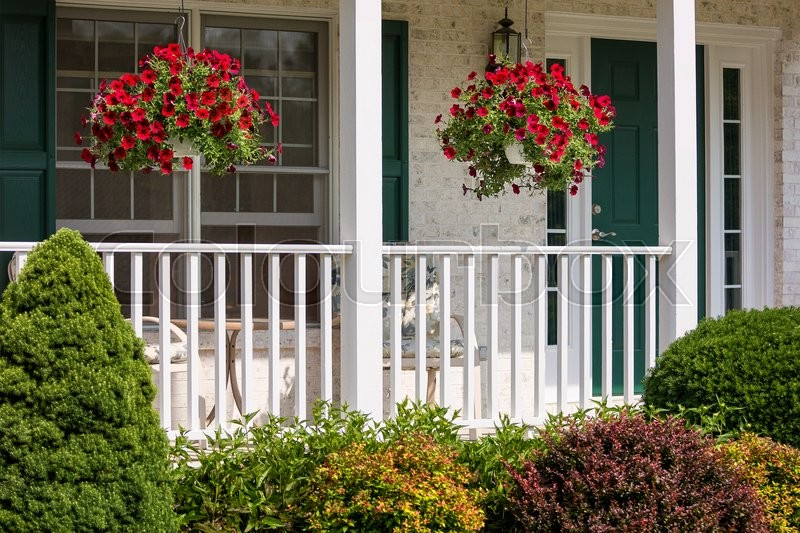 A Beautiful Landscaped American Front Porch With White Railings And Hanging Baskets With Red