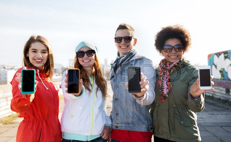 People, friendship, cloud computing, advertising and technology concept - group of smiling teenage friends showing blank smartphone screens outdoors, stock photo