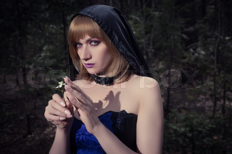 Halloween fantasy theme: witch girl in forest, stock photo