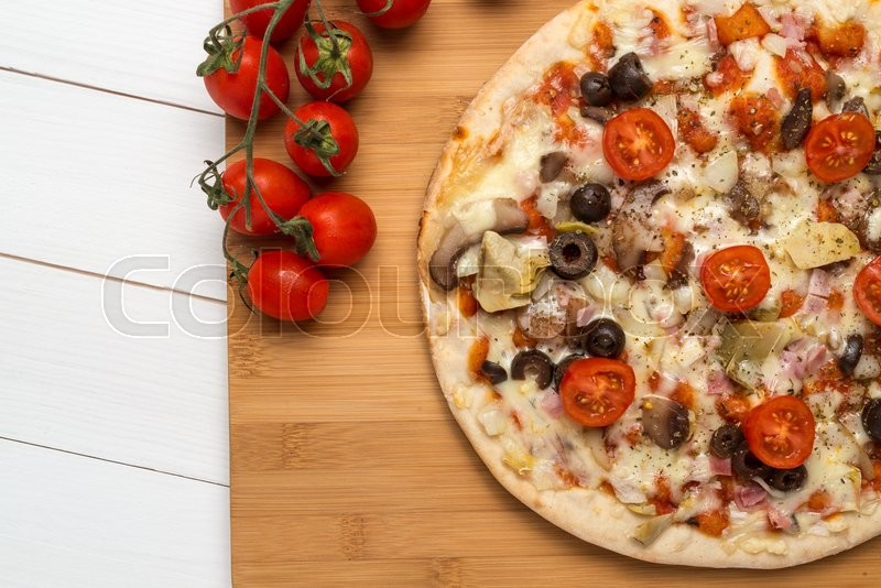 Pizza with bacon, olives and tomato on wooden table | Stock Photo ...
