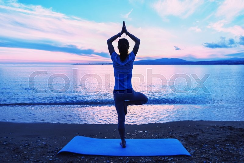 Woman doing yoga exercise in pose of tree on beach near the sea in summer in the morning, rear view, stock photo