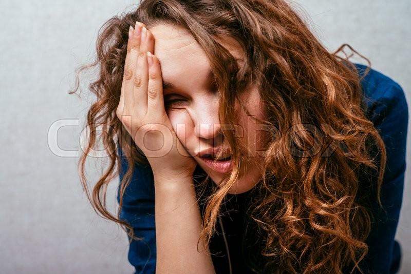 Curly girl feeling unwell. Gray background, stock photo