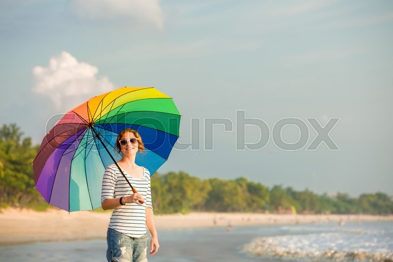 Young caucasian woman wearing white sunglasses with colourful rainbow umbrella looking at ocean on the Jimbaran beach on Bali before sunset. Travel, holidays, vacation, healthy lifestyle, tranquility concept, stock photo