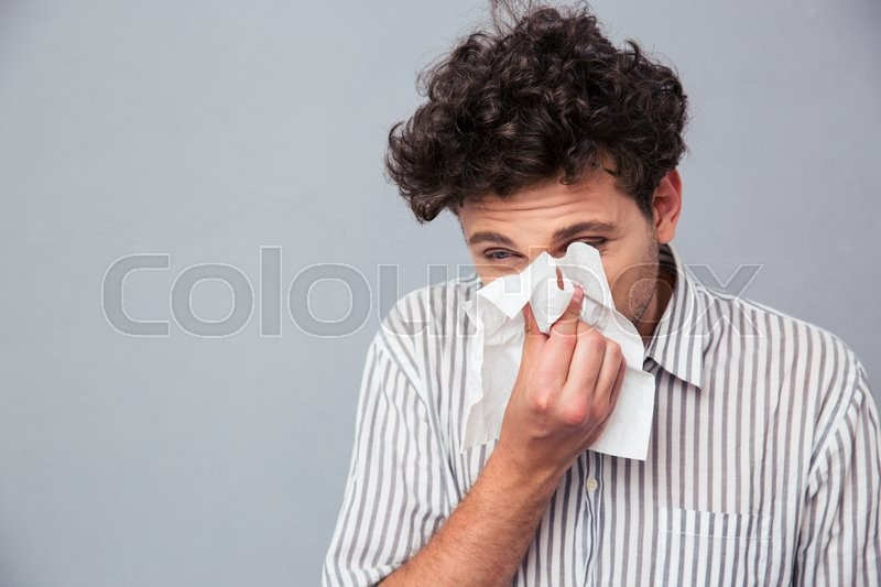 Portrait of a man blowing his nose over gray background, stock photo