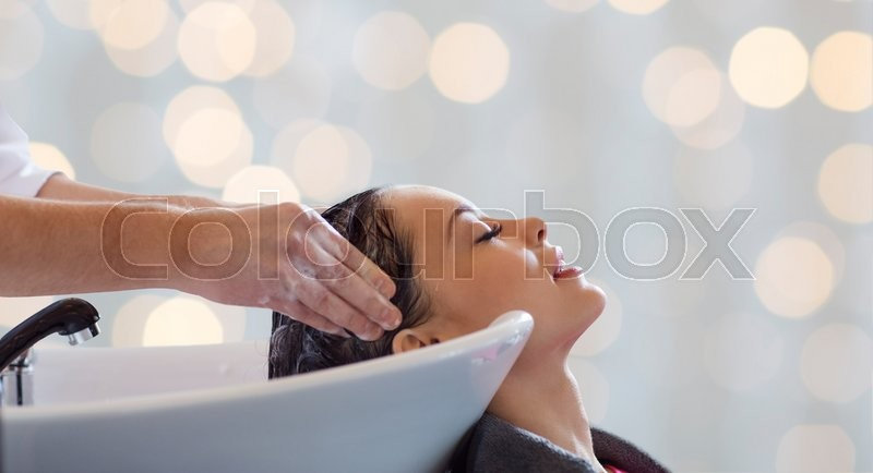 Beauty salon, hair care and people concept - hairdresser hands washing happy young woman head over holidays lights background, stock photo