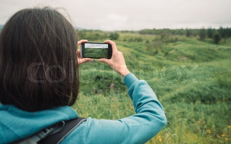 Hiker young woman taking photographs the beautiful summer landscape with mobile phone, stock photo