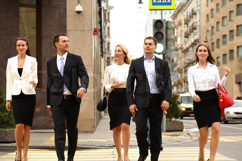 Full length portrait of a young Five successful business people crossing the street in the city center, stock photo